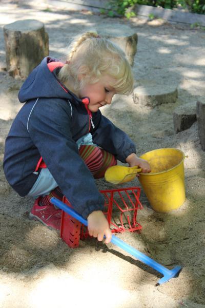 Pige der leger i sandkassen