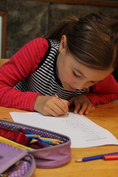 Pige der skriver på papir